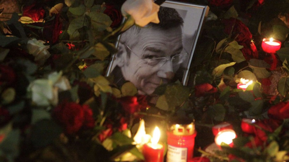 Candles and roses are placed next to the picture of Dominik Brunner on a railway platform at the train station of the Munich suburb of Solln