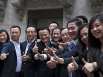 Alibaba founder Jack Ma and co-founder and VP Joseph Tsai pose with employees as they arrive for the company's IPO at the NYSE in New York