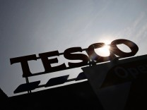 The signage of Tesco Extra is silhouetted against the sun in southwest London