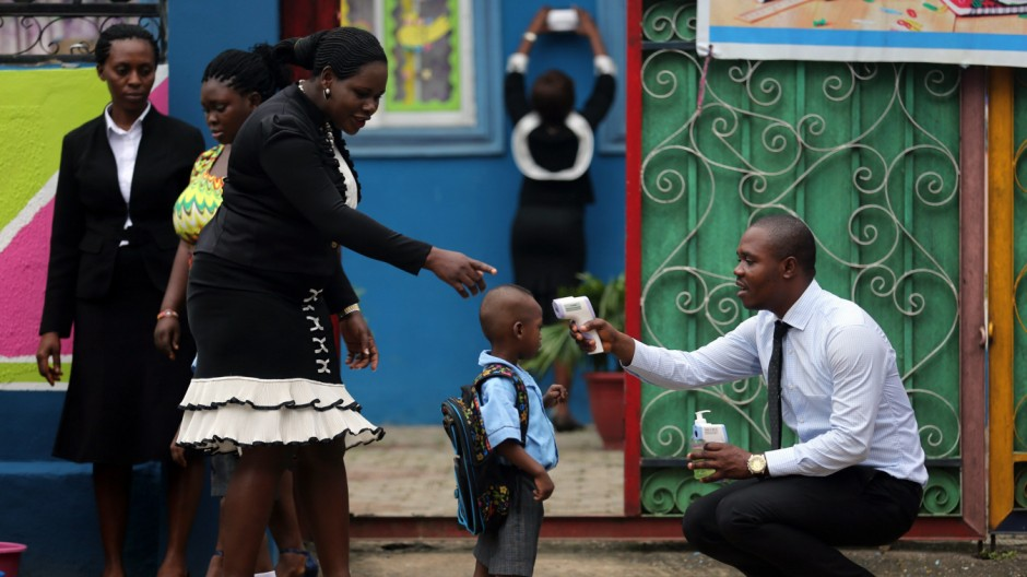 A school official takes a pupil's temperature using an infrared digital laser thermometer in front of the school premises, at the resumption of private schools, in Lagos