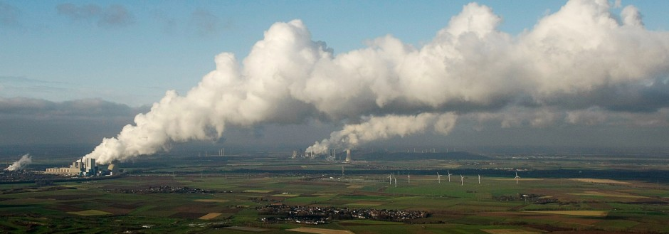 An aerial view shows steam billowing from the cooling towers of a coal power plant in the western town of Neurath