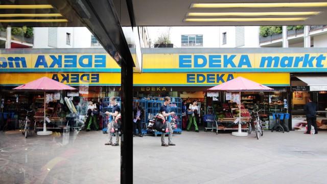 die Filiale eines Edeka Lebensmittelmarkt es spiegelt sich in einem Schaufenster in der Innenstadt M