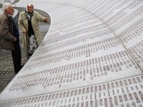 Bosnian Muslim couple Suhra Malic and Hasan Malic look at a memorial to victims of the 1995 Srebrenica massacre in Potocari near Srebrenica