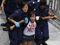 A protester reacts as she is dragged away by police after storming in government headquarters in Hong Kong