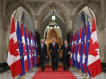 Canada's PM Harper walks with European Council President Van Rompuy and European Commission President Barroso in the Hall of Honour on Parliament Hill in Ottawa