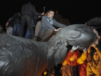 People react after a statue of Soviet state founder Vladimir Lenin was toppled by protesters during a rally organized by pro-Ukraine supporters in the centre of the eastern Ukrainian town of Kharkiv