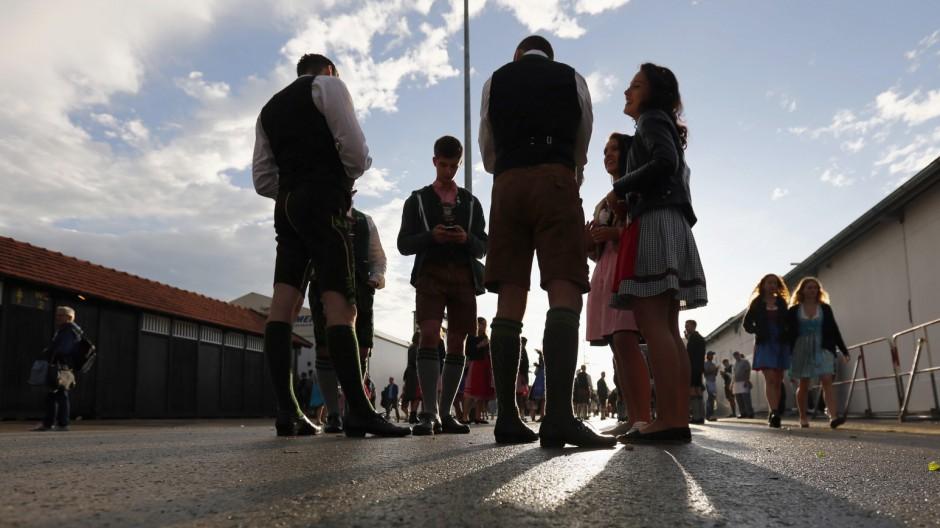Oktoberfest visitors wearing traditional Bavarian dirndl dresses and lederhosen wait outside a beer tent in Munich