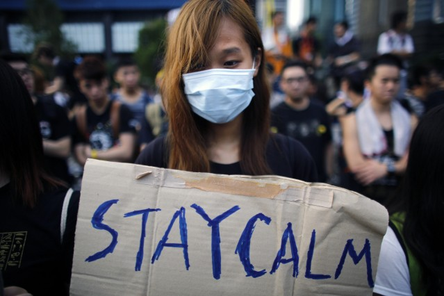 A student hold a sign as protesters gather around the Golden Bauhinia Square before an official flag raising ceremony to commemorate the Chinese National Day in Hong Kong