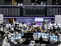 Visitors stand in front of the DAX board at the Frankfurt stock exchange