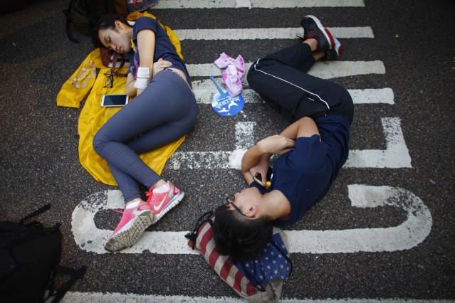 Protesters sleep as they block a street outside the government headquarters in Hong Kong