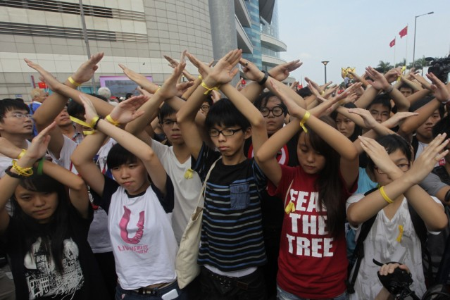 Scholarism founder Joshua Wong and other members gesture during a flag raising ceremony in Hong Kong