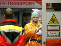 Medical staff members wearing sealed protective suits work during the arrival of an Ebola patient at the University Hospital Frankfurt in Frankfurt