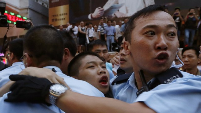 Pro-democracy protester bleeds in the month as he is escorted by the police after being beaten by anti-Occupy Central protesters at Hong Kong's shopping Mongkok district