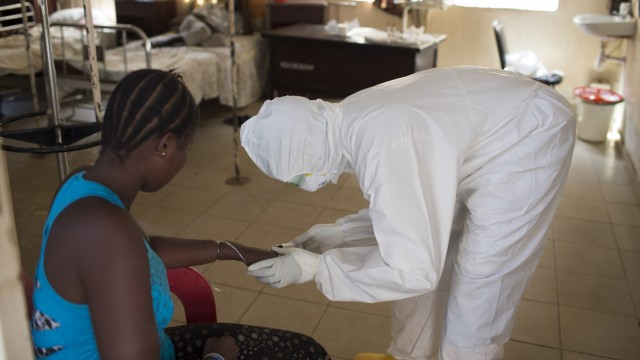 Health worker wearing protective equipment takes a blood sample from a patient at a ward for patients suspected of having the Ebola virus, at Rokupa Hospital