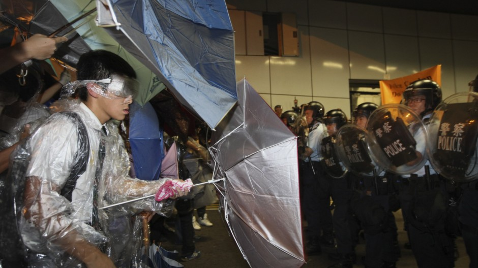 A student protester in his school uniform stands off with riot police inside a vehicle tunnel as pro-democracy protesters stormed in to block a road leading to the financial Central district in Hong Kong