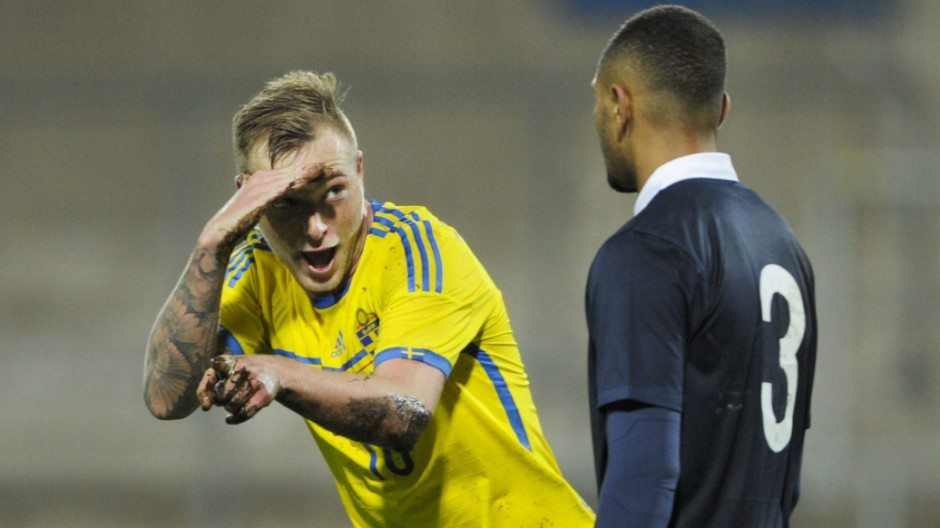 Sweden's Guidetti celebrates after a team mate scored as France's Kurzawa looks on during their UEFA U21 European Championships qualifying soccer match at Orjans Vall in Halmstad