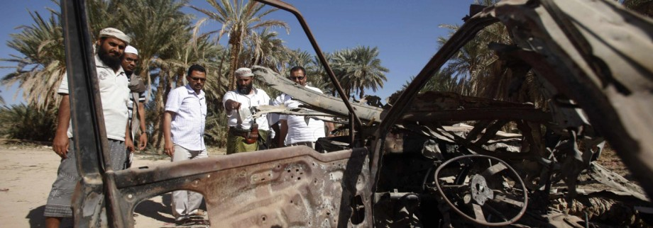 People talk to human rights activists next to debris left by a U.S. drone air strike that targeted suspected al Qaeda militants in August 2012, in the al-Qatn district