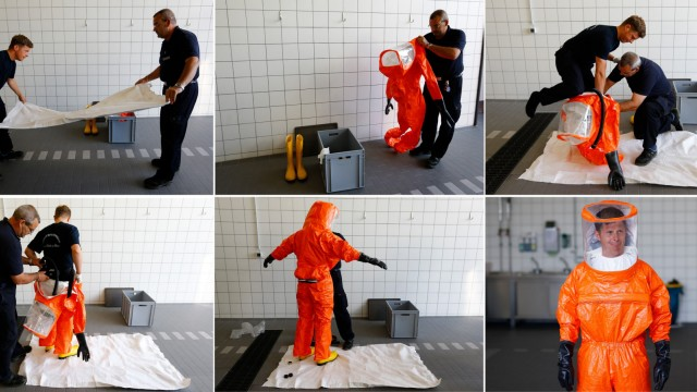 A combination of pictures shows fire brigade paramedic being assisted while putting on a sealed protective suit during a drill in Frankfurt