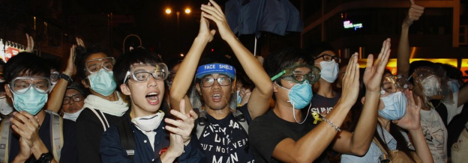 Pro-democracy protesters applaud after riot police retreated from a main road at Mong Kok shopping district in Hong Kong