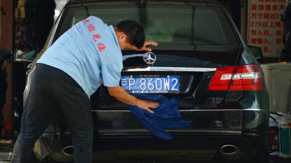 Chinesischer Arbeiter wäscht einen Mercedes in Beijing