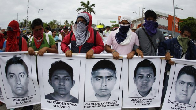 Students from the Ayotzinapa Teacher Training College carry photographs of missing students during a march in Acapulco