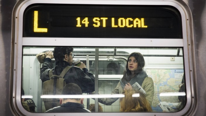 Commuters ride an L train for the morning commute a day after an announcement that the subway system had been used by a doctor now testing positive for Ebola in New York