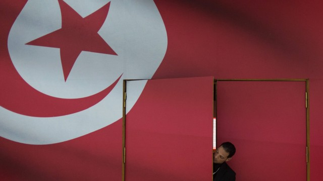 A security guard looks out from the entrance of a conference hall in the media center for 2014 Tunis