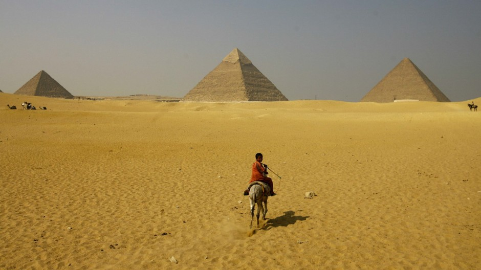 A boy rides a horse in front of the Great Pyramids of Giza on the outskirts of Cairo