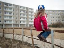 Kleines Mädchen sitzt auf Zaun in Plattenbau-Wohngebiet