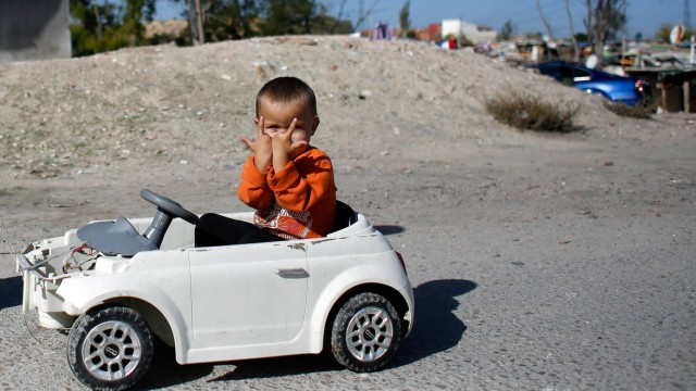 A child gestures to the camera as he is pushed around by a relative in his toy car in the shanty town settlement of 'El Gallinero' in the outskirts of Madrid