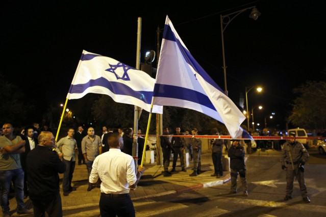 Israelis wave national flags next to security personnel securing an area in Jerusalem where a far-right activist was shot and wounded