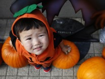 Shunto, wearing a Halloween outfit, sits on pumpkins before a Halloween parade in Kawasaki