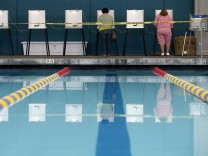 People fill out their ballots at a polling place at a swimming pool on Election Day in Los Angeles