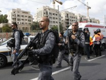 Israeli police officers walk at the scene of an attack in Jerusalem