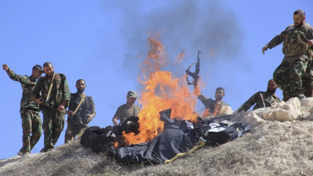 Forces of Syria's President Bashar al-Assad burn the flag of al Qaeda-linked Nusra Front, which they said was left behind by rebel fighters, in Zor al-Mahruqa village