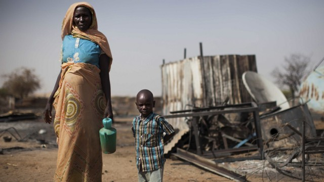 Handout showing a displaced mother and her child inspect the remnants of their burnt house in Khor Abeche