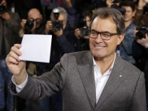 Catalan President Artur Mas holds up his ballot before voting in a symbolic independence vote in Barcelona