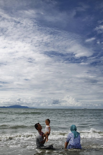 A Muslim family enjoys nice weather on the beach in Banda Aceh