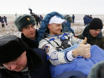 Ground personnel carry International Space Station crew member Gerst of Germany shortly after landing near the town of Arkalyk in northern Kazakhstan