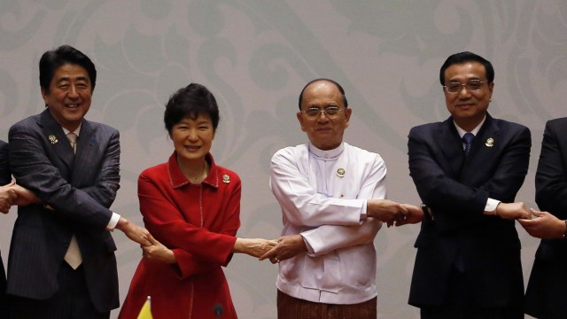 Japan's Prime Minister Shinzo Abe, South Korea's President Park Geun-Hye, Myanmar's President Thein Sein and China's Premier Li Keqiang hold hands as they pose for a family photo before the ASEAN Plus Three Summit