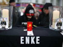 Young supporter of Germany's national goalkeeper Robert Enke writes in book of condolences outside headquarters of Germany's first Bundesliga soccer team Hanover 96 in Hanover