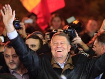 Romanian presidential candidate Klaus Iohannis celebrates his victory in the election run-off, with protesters in central Bucharest