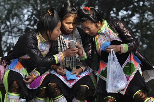 Ethnic Miao minority girls read a message from a mobile phone in Basha village of Congjiang county