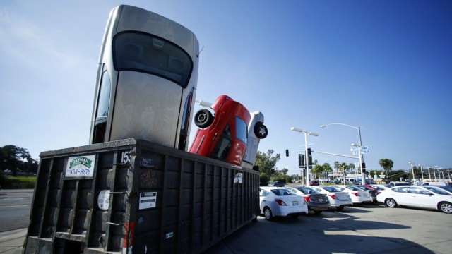 Used cars are shown tossed into a dumpster as an advertising display in front of a local car dealership in San Diego