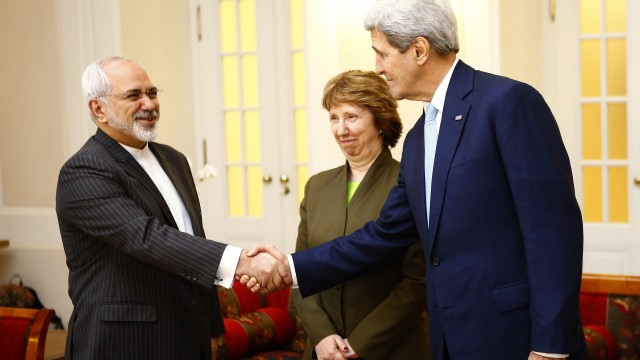 U.S. Secretary of State Kerry and Iranian FM Zarif shake hands as EU envoy Ashton watchesbefore a meeting in Vienna