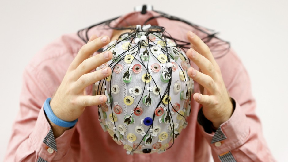 Test person Thiel poses with an electroencephalography cap which measures brain activity, at the Technische Universitaet Muenchen in Garching