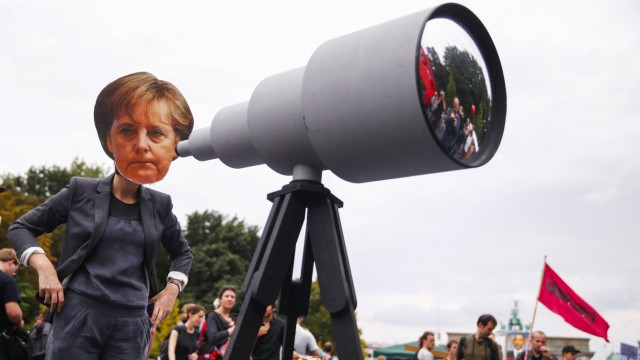 Woman wearing mask depicting German Chancellor Merkel stands during protest calling for protection of digital data privacy in Berlin