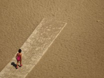 Child walks toward the shore of the Malagueta beach at the Mediterranean Sea in Malaga