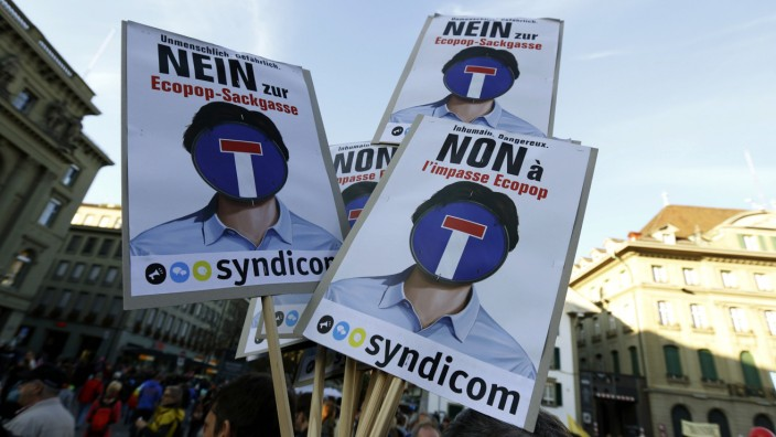 A banner against the Ecopop initiative is held by protestors in front of the parliament building during a demonstration in Bern