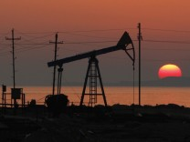 Oil derricks are silhouetted against the rising sun on an oilfield in Baku
